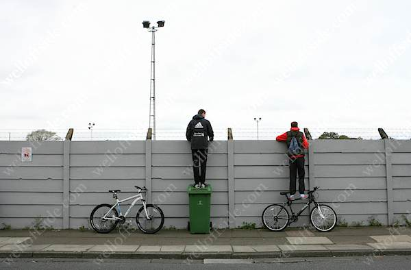 Fans stand on bikes and wheelie bins to see over the perimeter wall and barbed wire