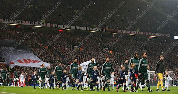 The two teams walk out onto the pitch in front of the Stretford End at Old Trafford