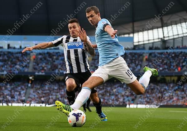 Mathieu Debuchy of Newcastle tackles Edin Dzeko of Man City