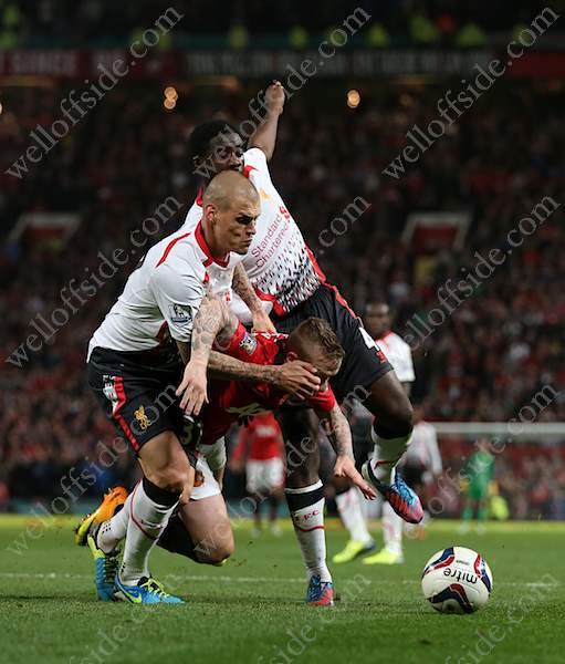 Alexander Buttner of Man Utd goes down under a challenge from Liverpool's Martin Skrtel (L) and Kolo Toure